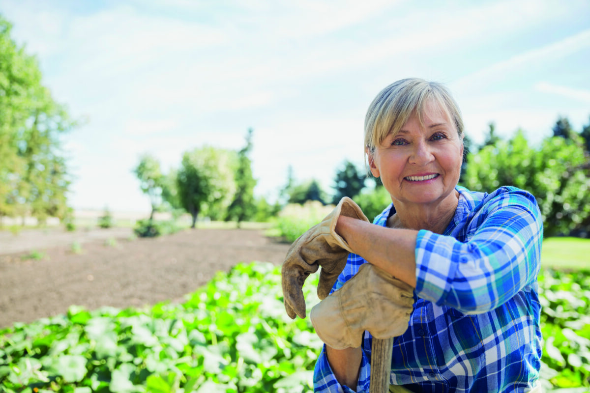 Portrait of smiling woman in sunny vegetable garden