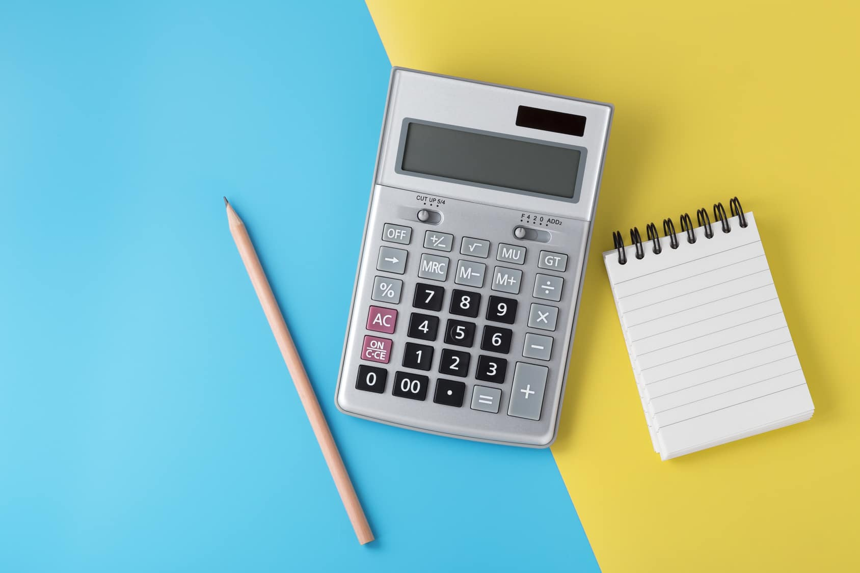 Calculator on light blue and yellow background with notepad and pencil, flat lay with space